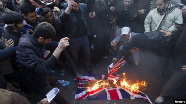 Protesters burn a British flag taken from the British Embassy in Tehran on November 29.