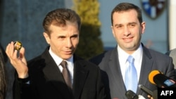 Georgian Prime Minister Bidzina Ivanishvili (left), flanked by Defense Minister Irakli Alasania, speaks to the media in February.