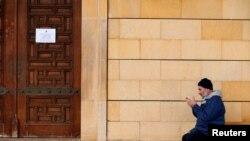 Мусульманин молится у стен закрытой мечети, Бейрут, Ливан, 20 марта 2020 года