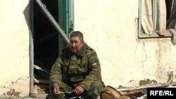 Офицер министерства по чрезвычайным ситуациям сидит у порога разрушенного от наводнения дома. Кызылагаш, 15 марта 2010 года.