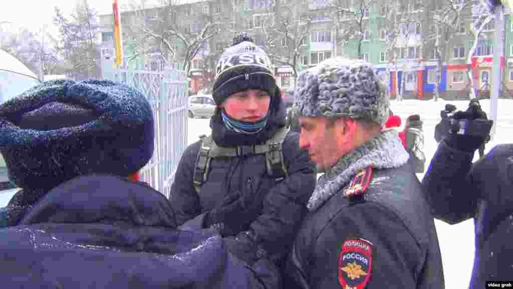 Полицейские задерживают сторонника Навального в Томске.