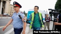 Корреспондент Азаттыка Манас Кайыртайулы пытается получить комментарий у сотрудника полиции. Алматы, 10 Июня 2019 года.