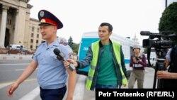 Корреспондент Азаттыка Манас Кайыртайулы пытается получить комментарий у сотрудника полиции на месте протестной акции. Алматы, 10 июня 2019 года.