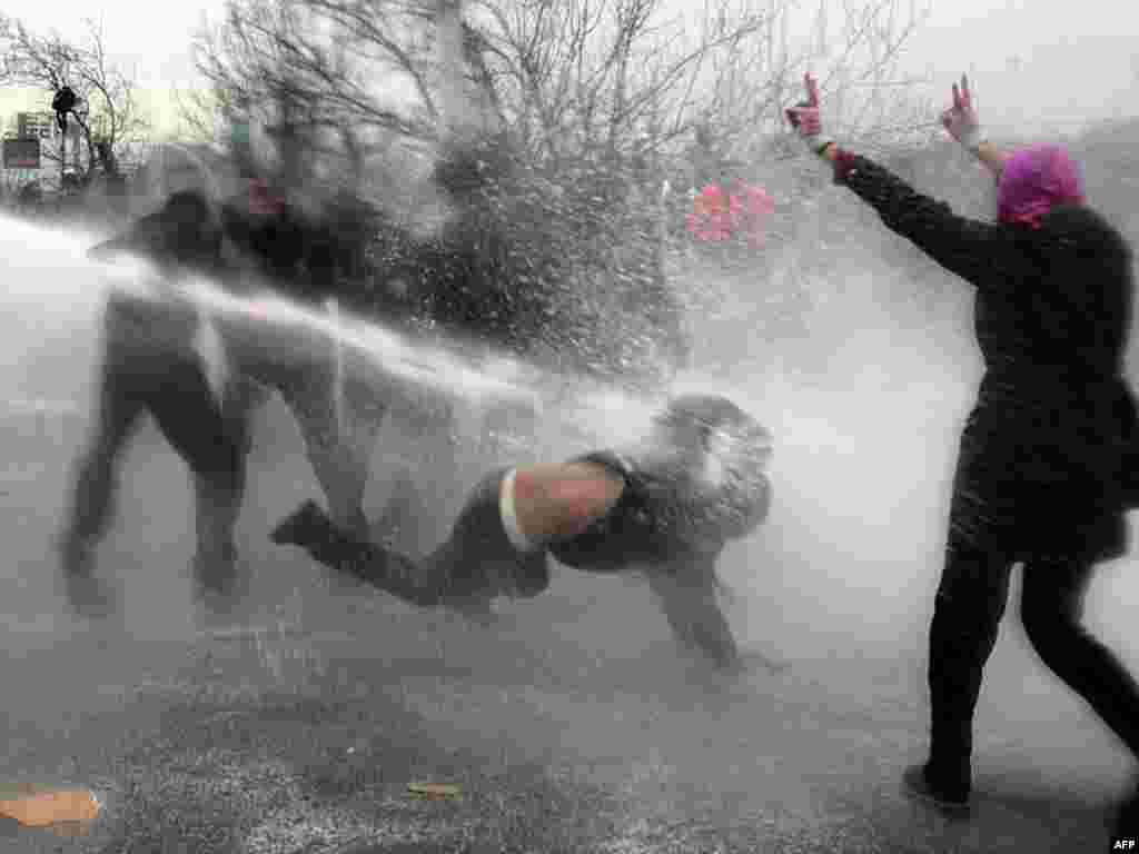 Demonstrators are sprayed by riot-police water cannons during a rally gathering 500 students against the Islamic-rooted government in Ankara on January 5. Students clashed with riot police on their way to the headquarters of the ruling Justice and Development Party. Photo by Adem Altan for AFP
