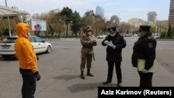 Сотрудники сил безопасности Азербайджана проверяют документы у прохожего в Баку, где ограничено передвижение на улице в связи со вспышкой коронавируса. 6 апреля 2020 года.