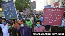 Restaurant workers shout slogans and hold placards during a protest against restrictions imposed by the authorities after indoor dining was banned following a rise in COVID-19 coronavirus cases in Karachi on December 3.