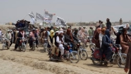 Pakistani supporters of the Taliban fly the Islamist group's signature white flags in the Afghan-Pakistan border town of Chaman on July 14.