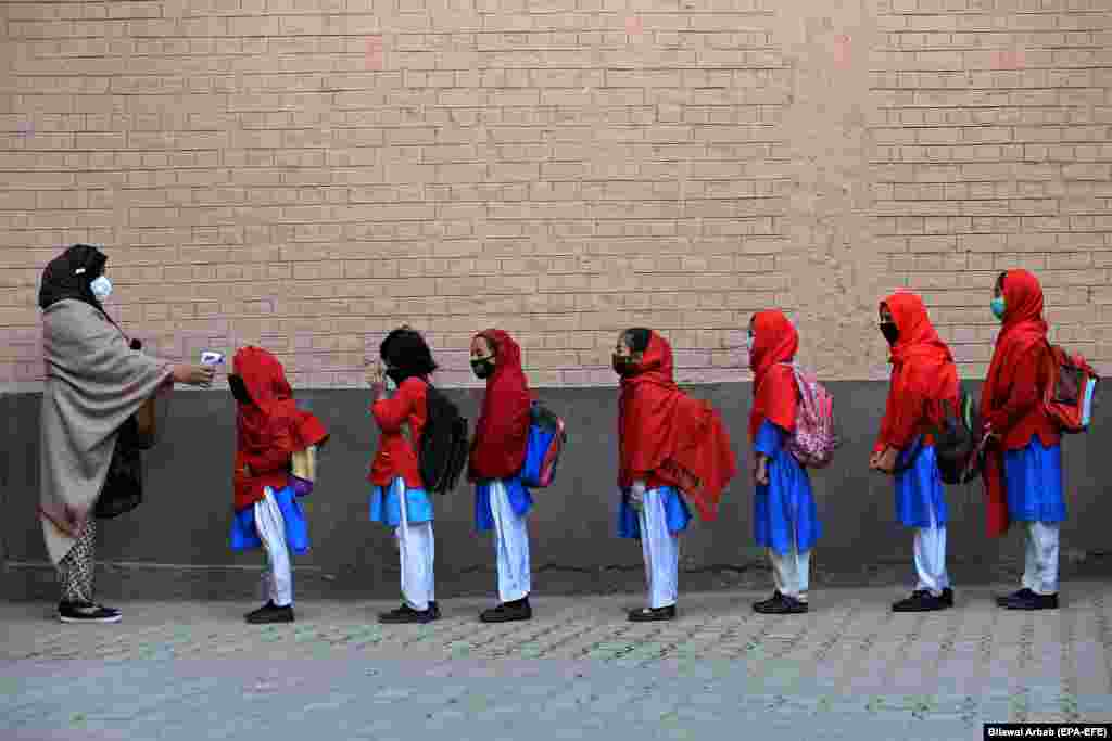 School staff check the temperatures of students as they arrive on the first day of primary school after the resumption of classes in Peshawar, Pakistan, amid the ongoing coronavirus pandemic. (epa-EFE/Bilawal Arbab)