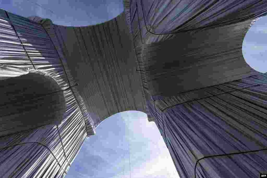 50-метровия военен монумент е опакован с 25 000 квадратни метра сребристо син полипропилен и 3 000 м червено въже.