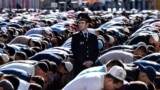 A police officer stands among Russian Muslims praying outside the central mosque in Moscow on July 5, 2016, during celebrations of Eid al-Fitr marking the end of the fasting month of Ramadan. / AFP PHOTO / KIRILL KUDRYAVTSEV