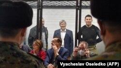 Собиқ президент Алмазбек Атамбаев (қафас ичида ўртадаги) суд жараёни пайтида.