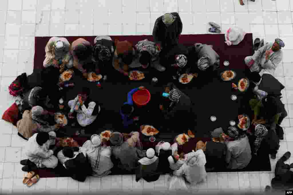 Afghan men break their fast during the holy month of Ramadan at the Hazrat-e Ali shrine in Mazar-e Sharif. (AFP/Farshad Usyan)