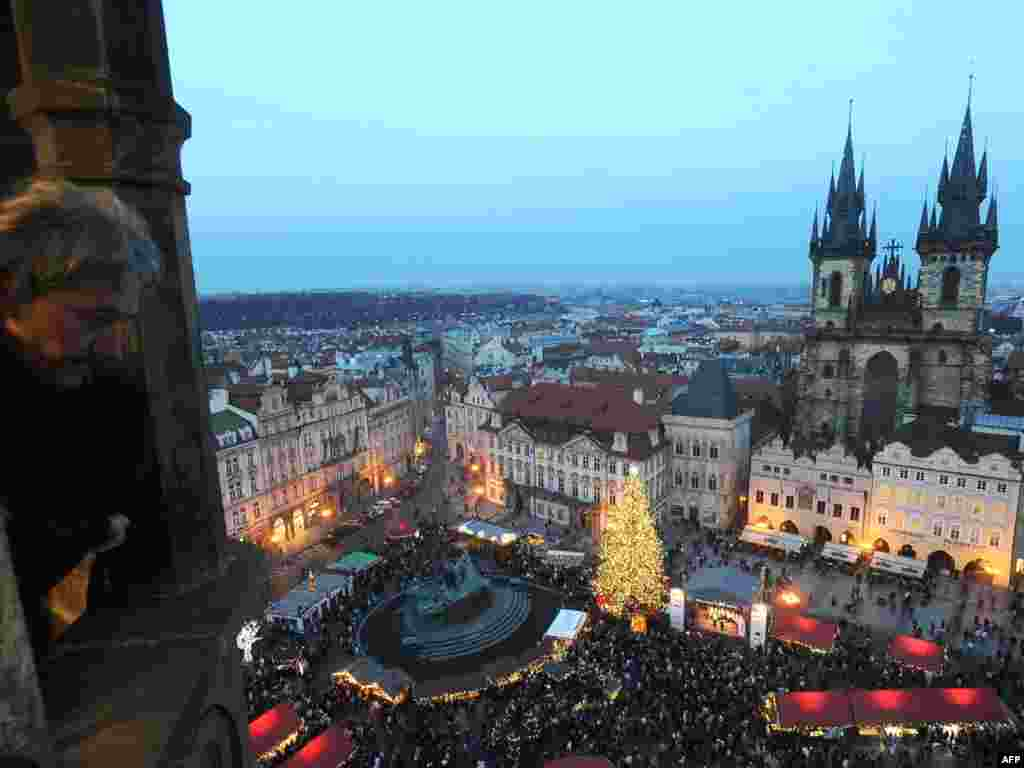 A man gazes down at the traditional Christmas market on the Old Town Square in Prague, Czech Republic. - Photo by AFP