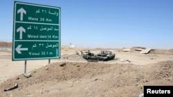 Rămășițele unu automobil al militanților Statului Islamic după ce a fost lovit de o rachetă americană, lîngă șoseaua care duce la lacul de acumulare de la Mosul, nordul Irakului, 21 august 2014.