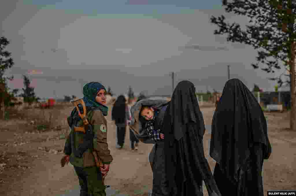 Veiled women, reportedly members of Islamic State and wives of the extremists, walk under the supervision of a female fighter from Kurdish-led Syrian Democratic Forces (SDF) in northeastern Syria. (AFP/Bulent Kilic)