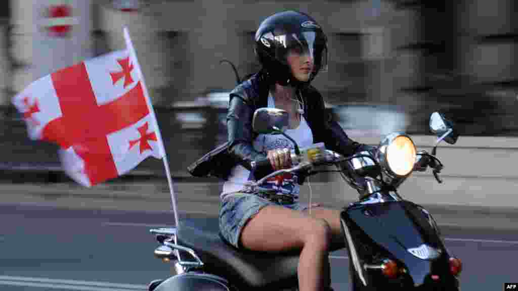 A supporter of the ruling United National Movement party rides a scooter in Tbilisi.