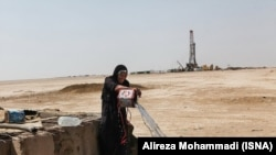 Gheyzaniyeh -- A local woman takes water from a well while in the background an oil well is visible.
