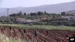 The Israeli village of Metulla, background, is seen from the Lebanese-Israeli border as Syrian farmers work in the village of Kfar Kila, in southeast Lebanon, Wednesday, May 20, 2020. Twenty years after Hezbollah guerrillas pushed Israel's last troops fro