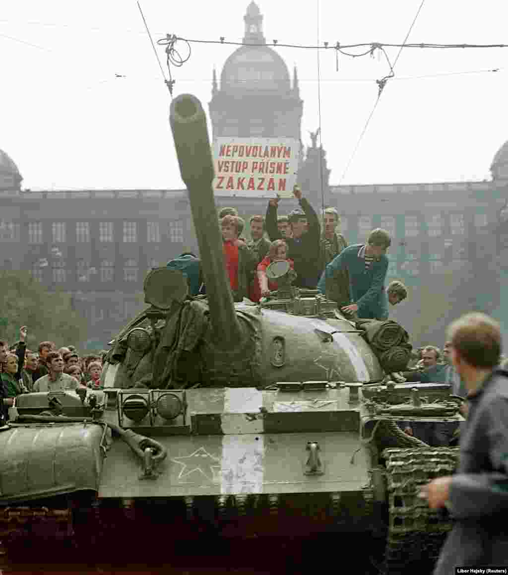 "Czechs ride a Soviet tank on Wenceslas Square at around 8-9 a.m. on August 21. At this stage, the atmosphere was still relatively relaxed, according to Hajsky. ""Lots of people essentially still didn't realize that it was a planned attack,"" he says. ""They thought it was a military exercise or something.... In this photo, you can see that there are kids on the tank. Like they were having a go on a fairground ride."""