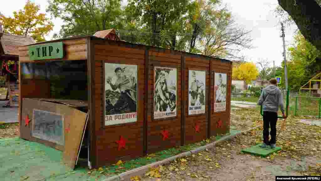 Неработающий тир с плакатами Второй Мировой войны в том же детском парке развлечений