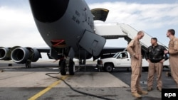 U.S. soldiers stand in front of military planes at the Manans air facilities near the Kyrgyz capital, Bishkek.