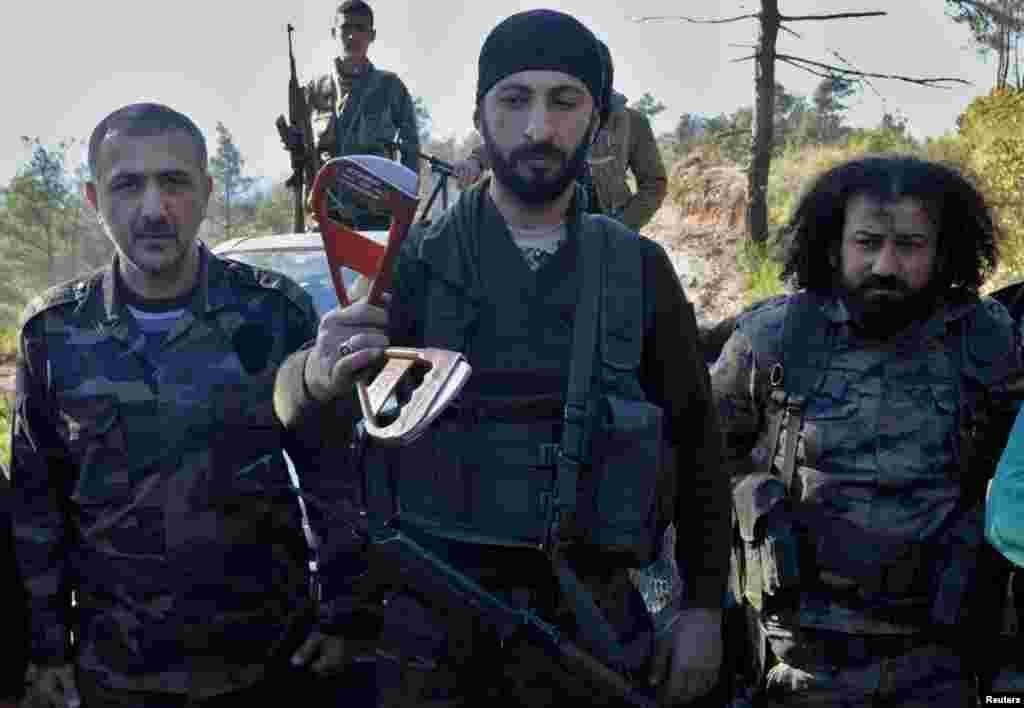 Алпаслан Челік (в центрі), заступник командира бригади сирійських тюркмен, тримає в руках частину парашута, що належав одному з членів екіпажу збитого російського літака