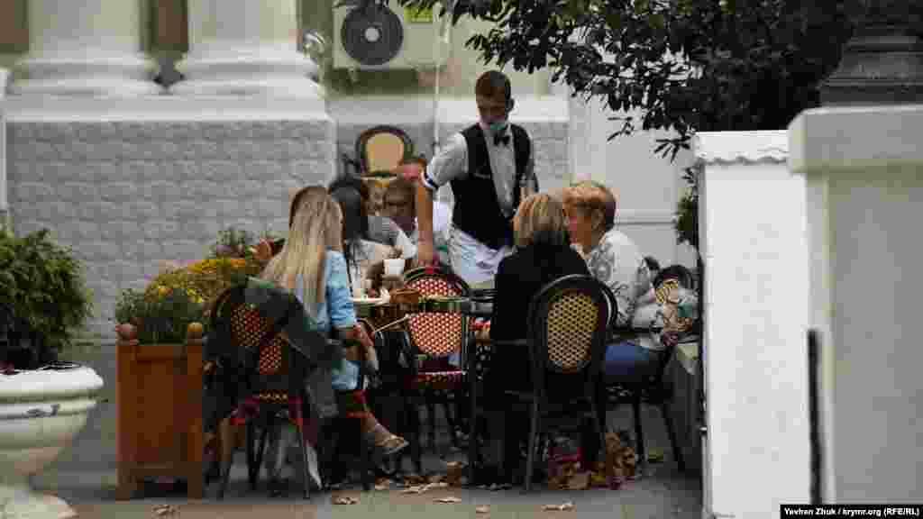 На летней террасе одного из севастопольских ресторанов посетители сидят без масок