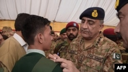Pakistani Army chief General Qamar Javed Bajwa gives his autograph to a student at the Army Public School, on the second anniversary of an attack on the school. in Peshawar on December 16.