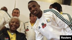 Nelson Mandela shakes hands with South African national team player Teko Modise in Johannesburg during the lead-up to the World Cup.