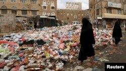 Женщины идут по улице с неубранным мусором в охваченном войной Йемене. Сана, 8 мая 2017 г.