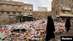Азамат соғысынан қираған Сана қаласының көшесінде үйілген қоқыс жанында кетіп бара жатқан әйелдер. Йемен, 8 мамыр 2017жыл.