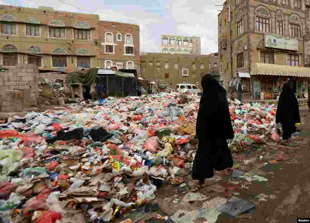 Women walk past a pile of rubbish bags on a street during a strike by garbage collectors demanding delayed salaries in Sanaa, Yemen, on May 8. (Reuters/Khaled Abdullah)