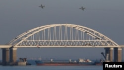 Russian fighters fly over the bridge connecting the Russian mainland with the Crimean Peninsula after three Ukrainian Navy vessels were stopped by Russian ships on November 25.