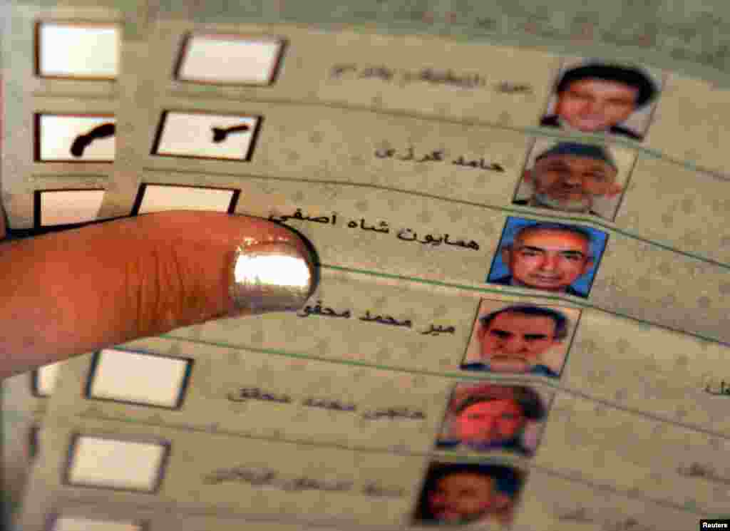 An Afghan election worker counts a vote for Karzai during the country's first post-Taliban presidential election, held on October 9, 2004. Karzai took the oath of office on December 7, 2004, for a five-year term as president.