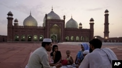 A Pakistani family waits to break their fast in the compound of the Mughal-era Shahi Mosque on August 3.