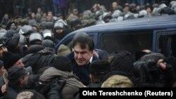 Михаил Саакашвилини коопсуздук кызматынын унаасына күчтөп отургузуп жаткан учур, Киев, 5-декабрь, 2017-жыл.