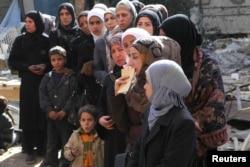Обитатели лагеря для сирийских беженцев в ожидании раздачи гуманитарной помощи