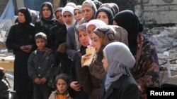 People wait to collect food aid distributed by United Nations Relief and Works Agency at the Yarmouk refugee camp. The camp has been suffering from extreme food shortages in recent months, which has left many malnourished or even starving.