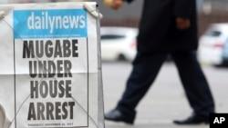 Харареде президент Роберт Мугабенің үйқамаққа алынған туралы газет хабарламасы жанынан өтіп бара жатқан адам. Зимбабве, 16 қараша 2017 жыл.