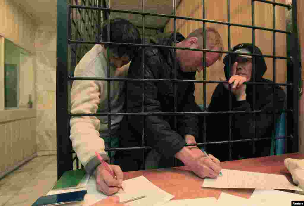 Illegal migrants from the former Soviet republics fill out forms as they wait in a holding cell at a police station in Krasnoyarsk in September 2013.