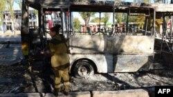 Ресейшіл сепаратист өртенген автобусты тексеріп жүр. Донецк, 1 қазан 2014 жыл. (Көрнекі сурет)