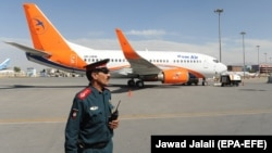 An Afghan police officer stands guard in front of a Boeing 737-500 of the Afghan carrier Kam Air at Kabul International Airport in Kabul. (file photo)