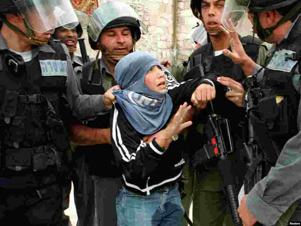 A young Palestinian protester is arrested by Israeli border police in Jerusalem's Old City, April 6, 2001 after clashes broke out following Friday's Muslim prayers. As Israel prepared for the weeklong Passover holiday, commemorating the biblical exodus of the Israelites from Egyptian slavery, the militant Islamic Jihad group vowed to avenge the killing of one of its West Bank leaders. REUTERS /Evelyn Hockstein