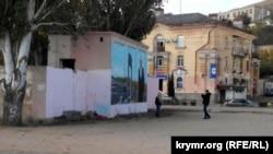 Парень фотографирует девушку на фоне граффити с изображением Владимира Путина на набережной Керчи