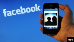 Apple iPhone 4 қалта телефоны Facebook компаниясының логотипінің фонында. Ганновер, 10 сәуір 2012 жыл