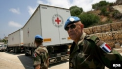 French UN peacekeeping soldiers walk behind Red Cross trucks at the Lebanese-Israeli border in 2008.