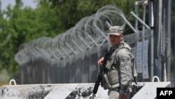 """Американский военный на КПП центра транзитных перевозок в день закрытия авиабазы """"Манас"""". 3 июня 2014 года."""
