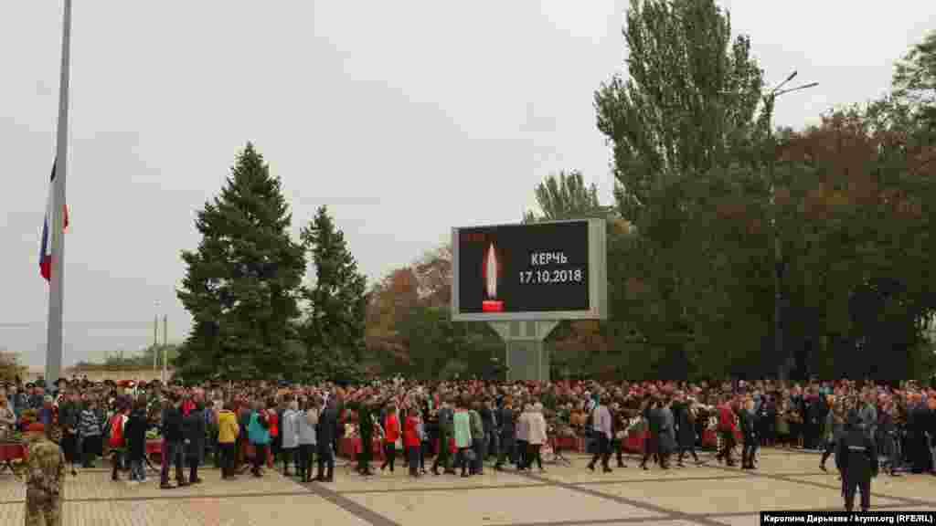На площади Ленина стоят в ряд 17 закрытых гробов с телами жертв трагедии.Рядом с каждым из них - фотографии и таблички с именами погибших. Играет траурная музыка. На большом экране изображена свеча и надпись «Керчь 17.10.2018»
