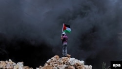 Palestine - Palestinian protester waves Palestine flag during clashes over the Jewish settlement of Qadomem at Kofr Qadom village, near West Bank city of Nablus, 13 June 2014