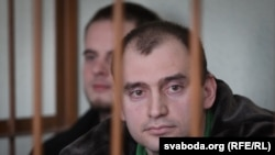 Alyaksandar Atroshankau sits in a barred cage in a Minsk court room.